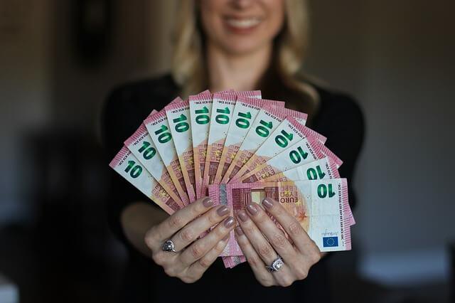 nainen pitaa setelinippua